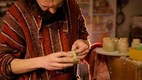 Professioneller männlicher Töpfer, der Becher in der Tonwarenwerkstatt herstellt Lizenzfreies Stockfoto