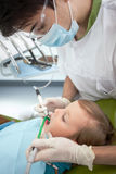 Professioneller männlicher Zahnarzt benutzt Bohrgerät für Stockbilder