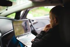 Professioneller mit einem Laptop im Auto stimmt abstimmendes Kontrollsystem ab und aktualisiert die Software und durch erhält zum Stockfoto