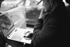 Professioneller mit einem Laptop im Auto stimmt abstimmendes Kontrollsystem ab und aktualisiert die Software und durch erhält zum Stockbilder