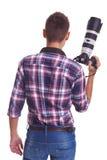 Professioneller männlicher Fotograf, der seine Kamera anhält Lizenzfreie Stockbilder
