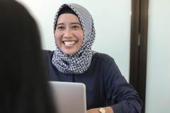 Professionelles junges hijab moslemisches Mädchen, das mit Laptop, junges moslemisches Fraueninterviewen arbeitet stockfotos