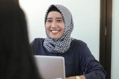 Professionelles junges hijab moslemisches Mädchen, das mit Laptop, junges moslemisches Fraueninterviewen arbeitet stockbild
