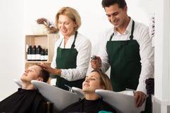 Professionellfrisörer som arbetar med hår av klienter i washi Royaltyfri Fotografi