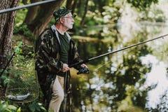 Professionelln åldrades fiskaren som rymmer en stång på flodstranden arkivfoton
