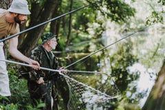 Professionelln avgick sportfiskaren som fiskar med hans son fotografering för bildbyråer