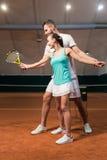 Professionelln gladde instruktören som undervisar en ung kvinna att spela tennis arkivfoto
