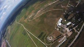 Professionelln hoppa fallskärm förklädet som flyger ovannämnda gröna fält extremt landning lager videofilmer