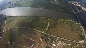 Professionelln hoppa fallskärm förklädet som flyger ovannämnda gröna fält, floden extremt höjd arkivfilmer