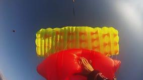 Professionelln hoppa fallskärm förklädet som flyger ovannämnda gröna fält wind extremt höjd arkivfilmer