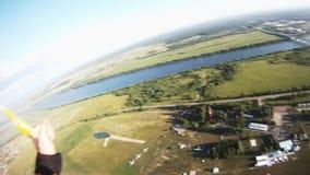 Professionelln hoppa fallskärm förklädet som flyger ovannämnda gröna fält wind extremt landning arkivfilmer
