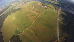 Professionelln hoppa fallskärm förklädet som flyger ovannämnda gröna länder soligt extremt höjd arkivfilmer