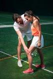Professionelln uppsökte tennisinstruktören som arbetar med den unga kvinnan royaltyfri foto