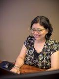 Professionista femminile di mente carriera che per mezzo del computer portatile fotografie stock libere da diritti