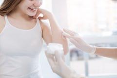 Professionista professionale che prova nuova crema medica su pelle paziente sul lavoro Immagini Stock