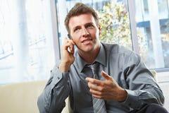 Professionista sorridente sul telefono con il gesto Fotografia Stock