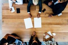 Professionisti corporativi che si incontrano intorno ad una tavola con le pagine in bianco Immagini Stock