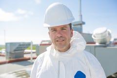 Professionnel dans l'uniforme protecteur, gants dans le toit pour le nettoyage images stock