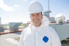 Professionnel dans l'uniforme protecteur, gants dans le toit pour le nettoyage image libre de droits