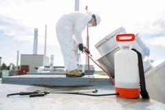 Professionnel dans l'uniforme protecteur, masque, gants dans le toit pour le nettoyage photo libre de droits
