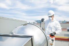 Professionnel dans l'uniforme protecteur, masque, gants dans le toit pour le nettoyage photo stock