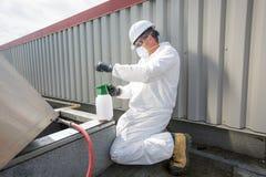 Professionnel dans l'uniforme protecteur, masque, gants dans le toit pour le nettoyage photographie stock libre de droits