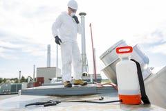 Professionnel dans l'uniforme protecteur, masque, gants dans le toit pour le nettoyage image stock