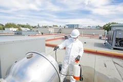 Professionnel dans l'uniforme protecteur, masque, gants dans le toit pour le nettoyage photos libres de droits