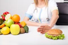 Professionnel de la santé éloignant l'hamburger Photos stock