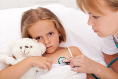 Professionnel de la santé contrôlant la petite fille malade Image libre de droits