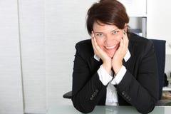 Professionnel de sourire d'affaires à son bureau photographie stock libre de droits