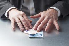 Professionnel masculin de pensée de finances avec l'argent sur son bureau Image libre de droits