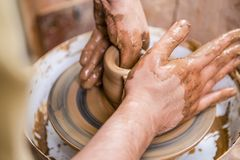 Professions and Craftmanship Concepts. Closeup of Dirty Male Hands. Working with Clay on Potter`s Wheel Inside of Workshop. Horizontal Image Composition royalty free stock photos