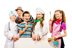 Professions. A group of children dressed in costumes of different professions holding white board. Isolated over white Royalty Free Stock Image