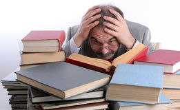 Professor. Single male is reading a book. Sitting behind a pile of books. Holding head in hands stock image