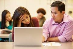 Professor alto Helping Stressed Pupil na classe foto de stock