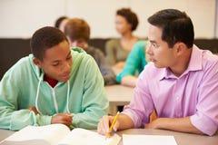 Professor alto Helping Student With escrito o trabalho fotografia de stock royalty free