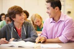 Professor alto Helping Student With escrito o trabalho fotos de stock