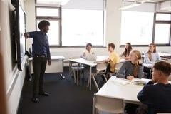 Professor alto masculino Standing Next To Whiteboard interativo e lição de ensino fotos de stock