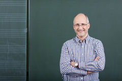 Professor With Arms Crossed Standing Against Chalkboard Stock Photo