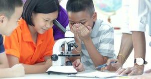 Professor asiático que expande ao estudante na turma de Biologia com microscópio filme
