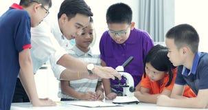 Professor asiático que expande ao estudante na turma de Biologia com microscópio vídeos de arquivo