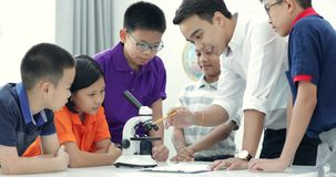 Professor asiático que expande ao estudante na turma de Biologia com microscópio video estoque
