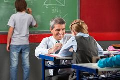 Professor Assisting Schoolgirl At Desk Stock Photos
