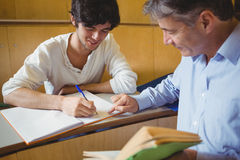 Professor assisting a student with his study. In classroom Stock Photos