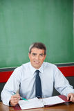Professor With Binder And Pen Sitting At Desk. Portrait of confident male professor with binder and pen sitting at desk in classroom Royalty Free Stock Image