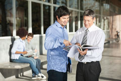 Professor With Books Explaining Student On Campus Royalty Free Stock Image