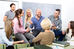 Professor chatting with students. Happy professor chatting with his smiling graduates after a lecture royalty free stock images