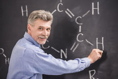 Professor. Of chemistry writes on the blackboard formula in University Stock Photos