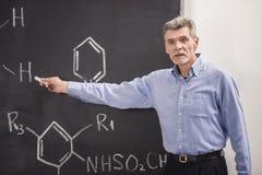 Professor. Of chemistry writes on the blackboard formula in University royalty free stock photo